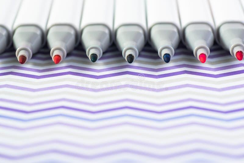 Kleurenmarkeerstiften op Witte golvende Achtergrond worden geïsoleerd die stock foto