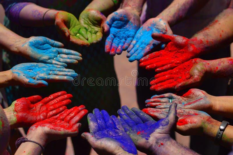 Kleurenpoeder op handen tijdens holifestival dichtbij Pune stock foto