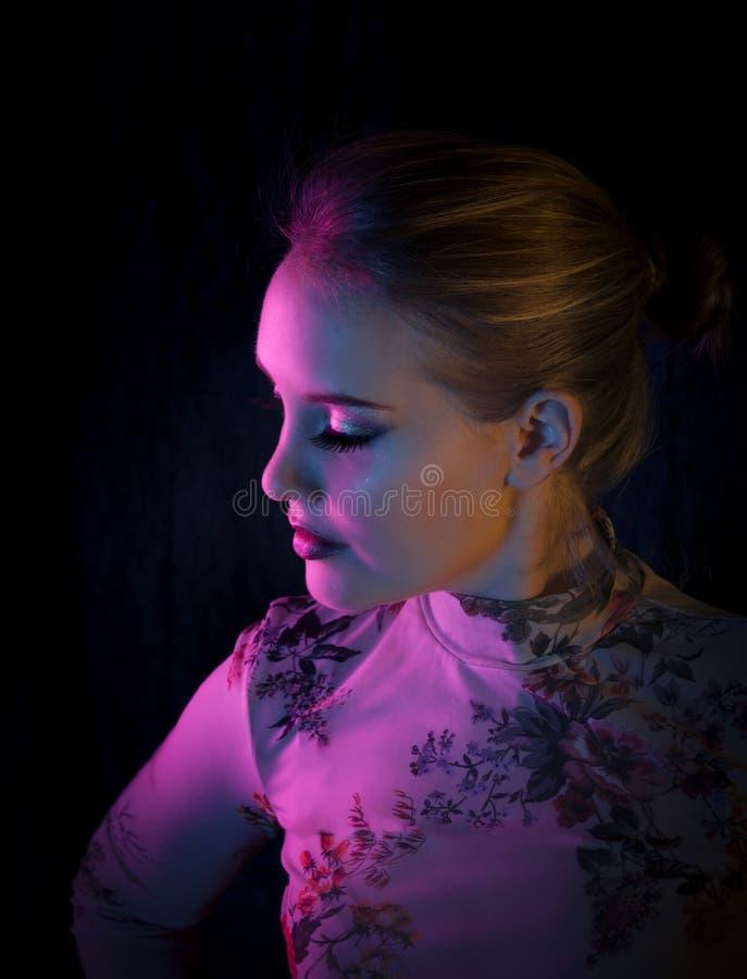 Kleurenportret van een mooie blonde vrouw die in een creatief kleurrijk licht van roze, oranje en blauw poseren royalty-vrije stock afbeeldingen