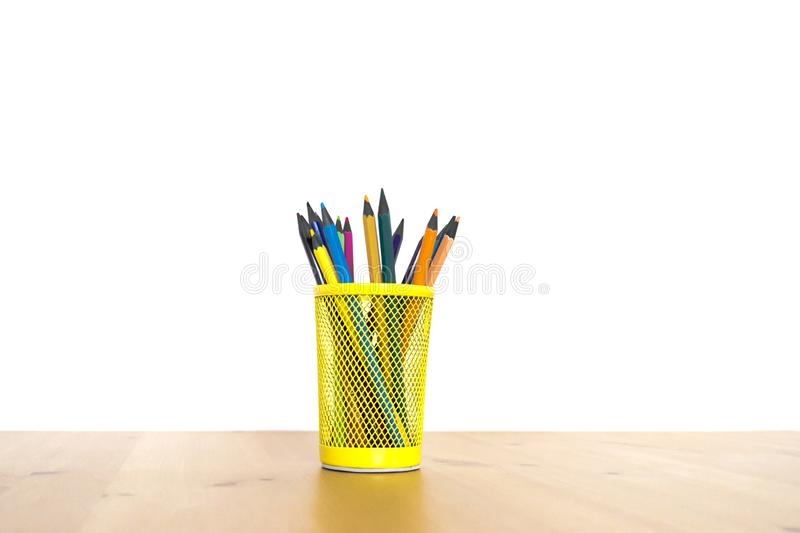 Kleurenpotloden in een geel glas op een houten lijst aangaande een witte achtergrond royalty-vrije stock fotografie