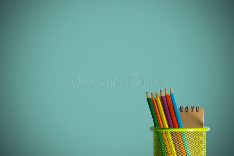 Kleurenpotloden in een groene houdersmand stock fotografie