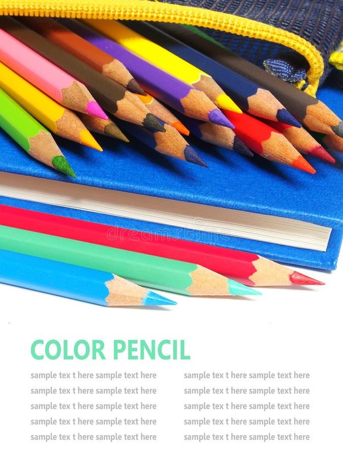 Kleurenpotloden en een blauw die notaboek op witte achtergrond wordt geïsoleerd stock afbeeldingen