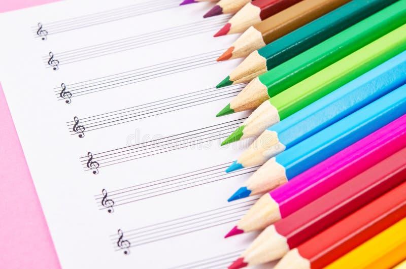 Kleurenpotloden en lege muzieknoten stock foto