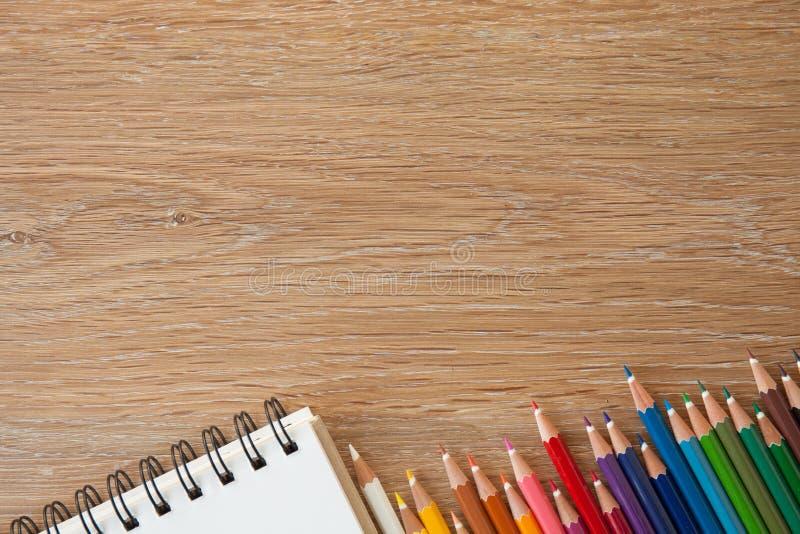 Kleurenpotloden met notitieboekje stock foto's