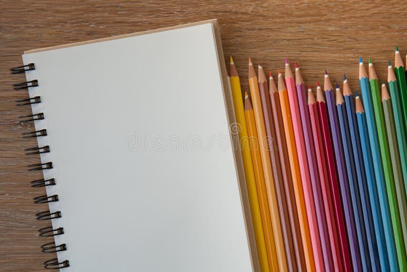 Kleurenpotloden met notitieboekje stock fotografie