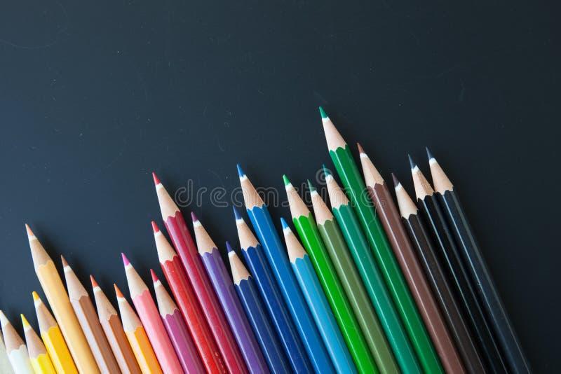 Kleurenpotloden op blackborad stock afbeeldingen