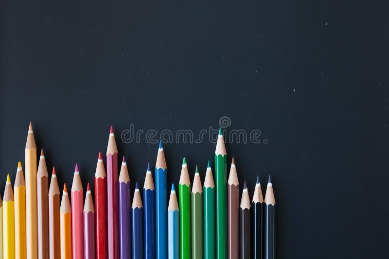 Kleurenpotloden op blackborad stock foto