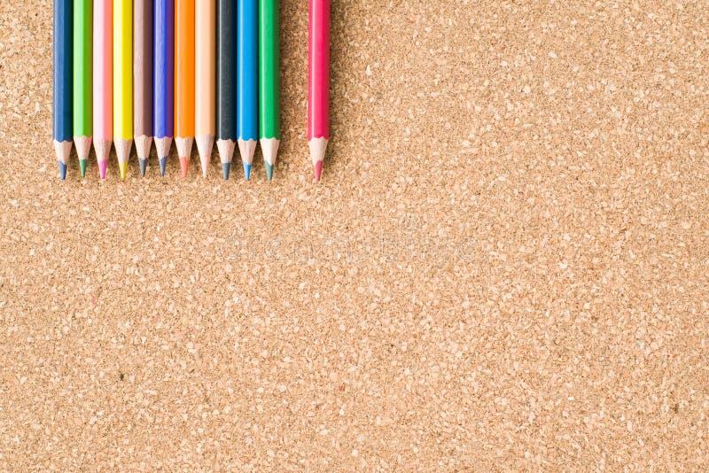 Kleurenpotloden op cork raadsachtergrond royalty-vrije stock afbeeldingen