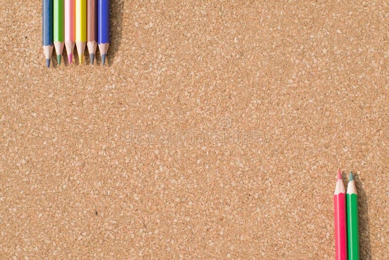 Kleurenpotloden op cork raadsachtergrond royalty-vrije stock foto's