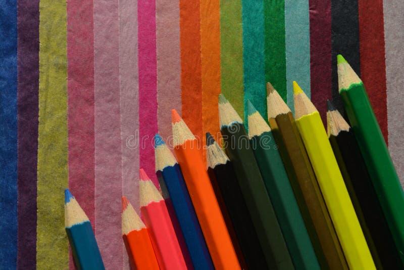 Kleurenpotloden op een multicoloured papieren zakdoekjeachtergrond stock afbeeldingen