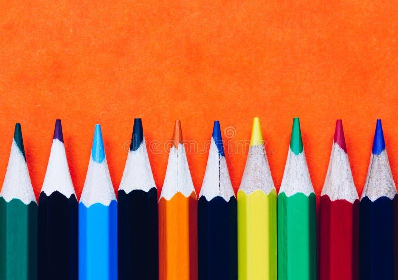 Kleurenpotloden op oranje achtergrond worden geïsoleerd die Sluit omhoog van gekleurde regenboogpotloden voor tekening, concept h stock afbeelding