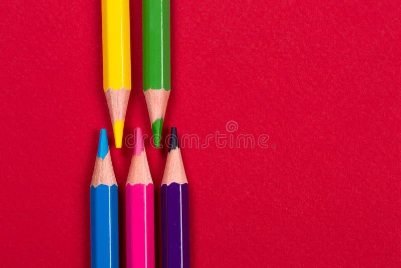 Kleurenpotloden op rood document van linkerkant stock afbeeldingen