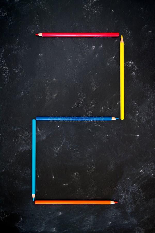 Kleurenpotloden op schoolbord die numeriek alfabet 2 maken stock foto