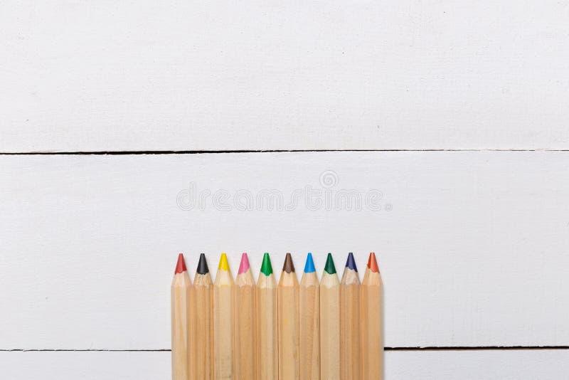 Kleurenpotloden op witte houten achtergrond royalty-vrije stock afbeeldingen