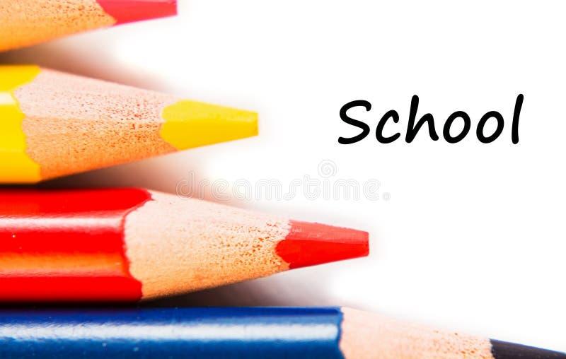 Kleurenpotloden in rij op witte achtergrond wordt geïsoleerd die Tekstschool royalty-vrije stock foto