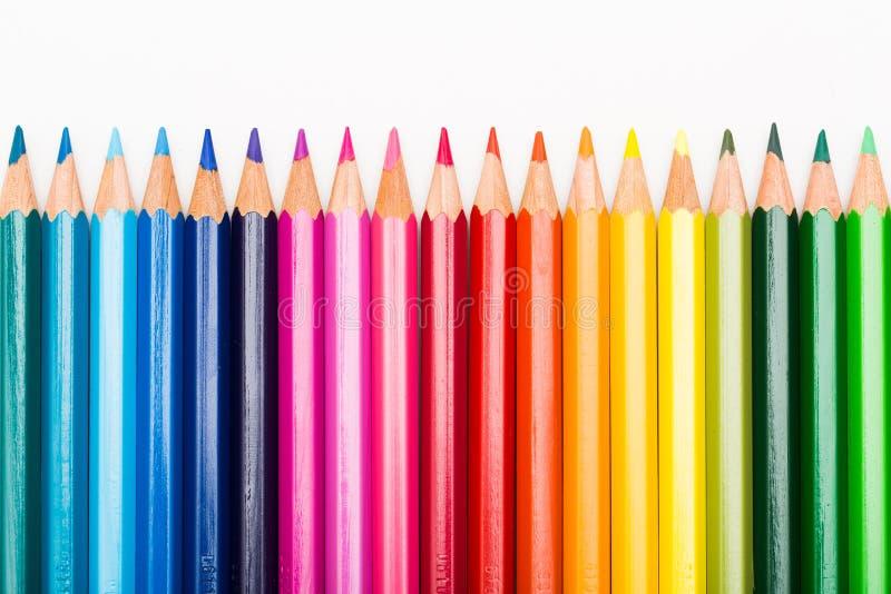 Kleurenpotloden in rij worden opgesteld die stock afbeeldingen