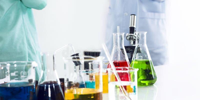 Kleurenwater in reageerbuis en beker Exemplaarruimte op wit laboratorium stock fotografie