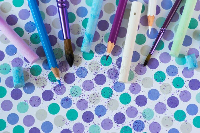 Kleurkrijtje en pancil op de pastelkleurachtergrond stock foto
