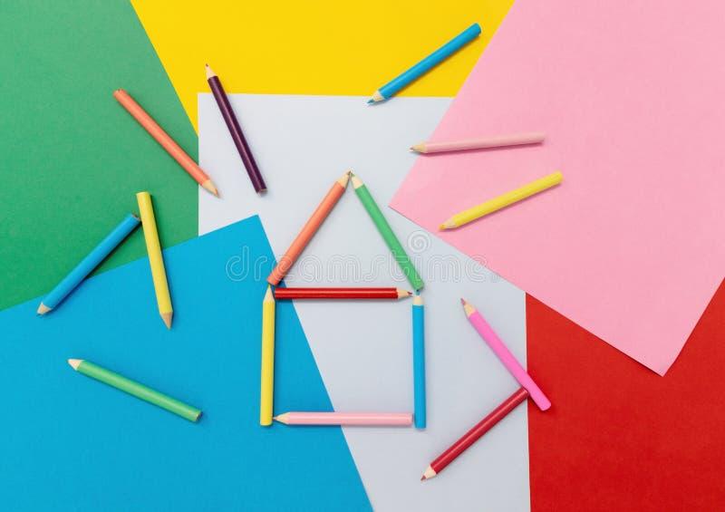 Kleurpotloden in de vorm van een huis op gekleurd document stock afbeeldingen