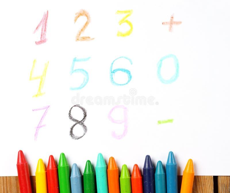 Kleurpotloden die op een document met geschilderd cijfer, aantal, teken liggen royalty-vrije stock fotografie
