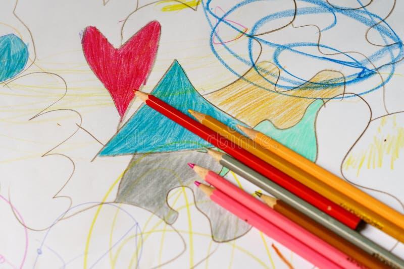 Kleurpotloden die op een document met harttekening liggen stock foto