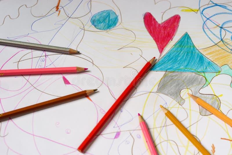 Kleurpotloden die op een document met harttekening liggen stock fotografie