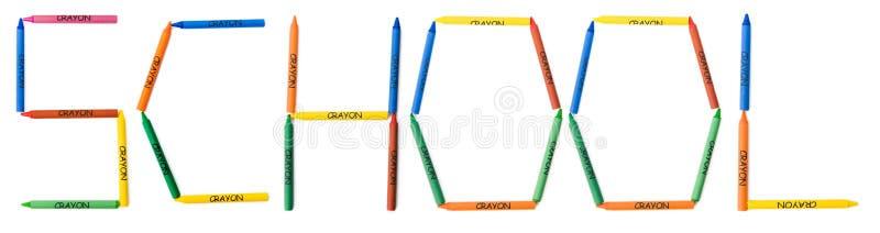 Kleurpotloden die School spellen stock foto