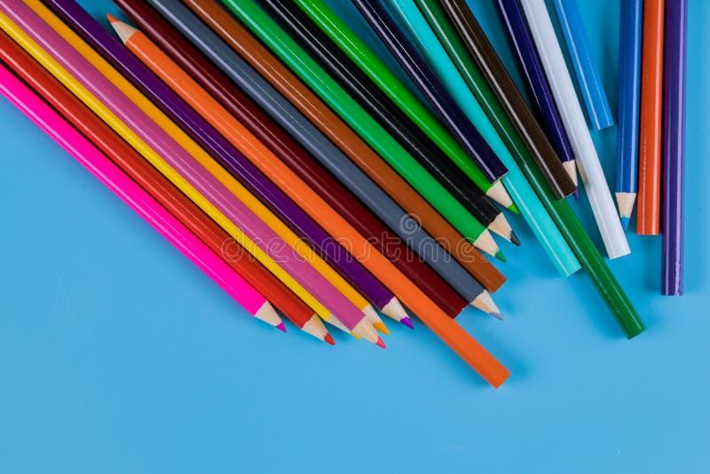 Kleurpotloden op blauwe achtergrond voor kunst en school stock afbeelding