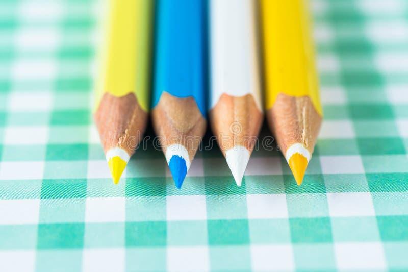 Kleurpotloden op een pastelkleurachtergrond van een kooi met ruimte voor tekst stock fotografie