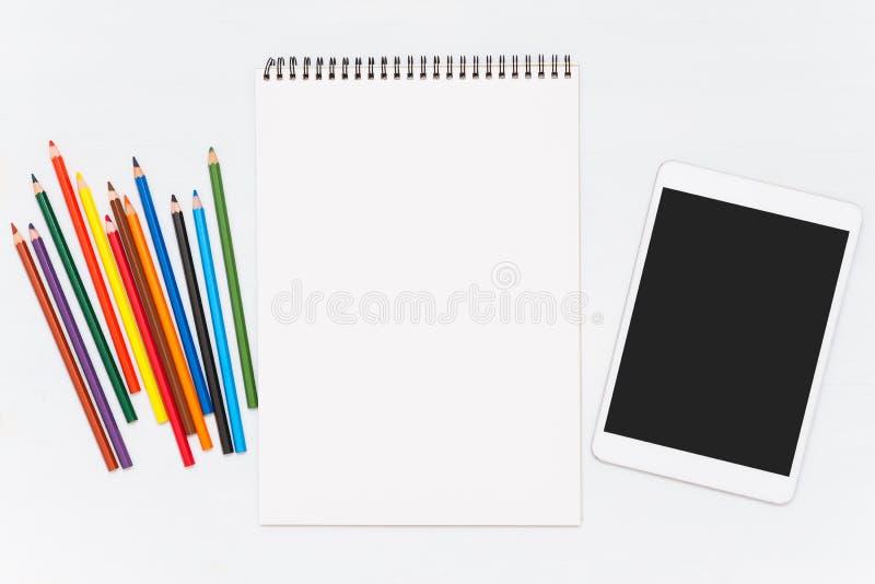 Kleurpotloden op houten lijst Lege notitieboekje en tablet royalty-vrije stock fotografie