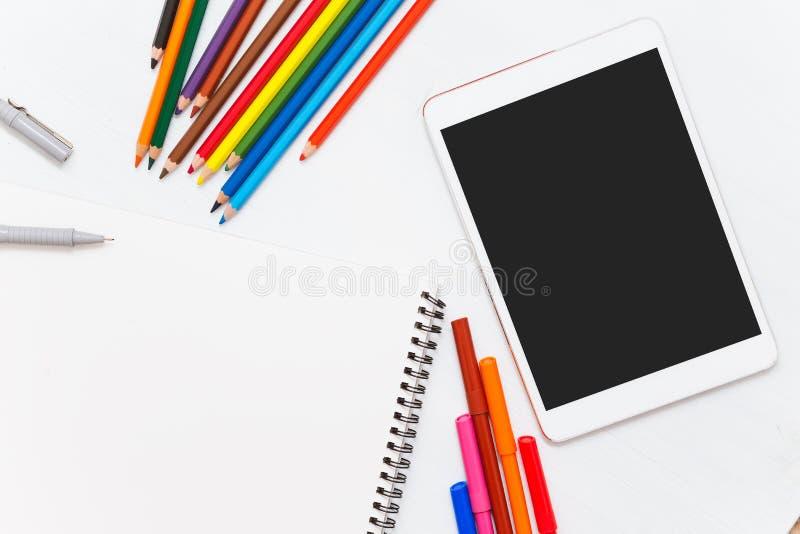 Kleurpotloden op houten lijst Lege notitieboekje en tablet royalty-vrije stock afbeeldingen