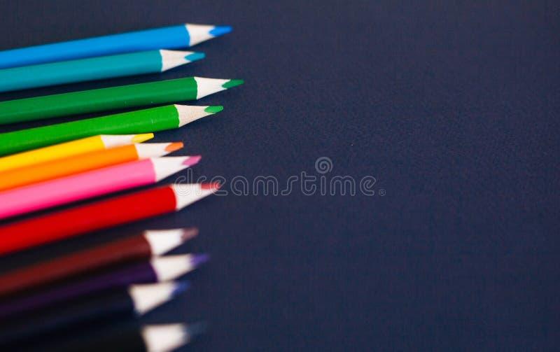 Kleurpotloden tegen donkerblauwe achtergrond Sluit omhooggaande en selectieve nadruk royalty-vrije stock fotografie