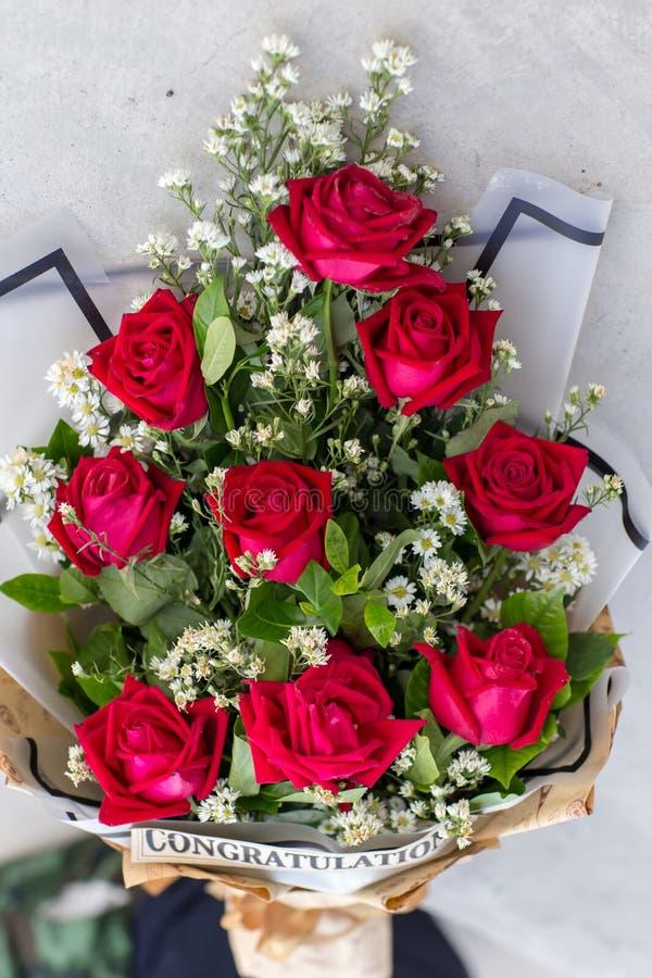 Kleurrijk boeket van verse bloemen tegen bakstenen muur Sluit omhoog van rode rozen stock foto