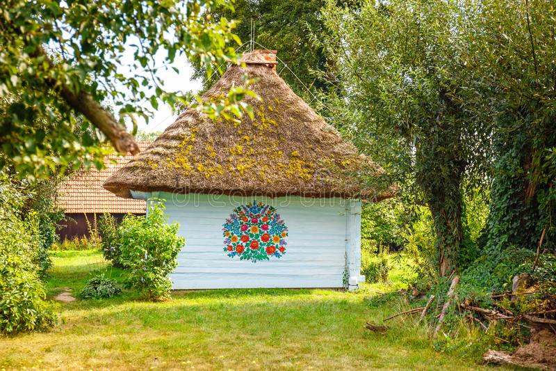 Kleurrijk die huis met bloemen op muren en zonnewijzer in het dorp van Zalipie, Polen worden geschilderd Het royalty-vrije stock fotografie