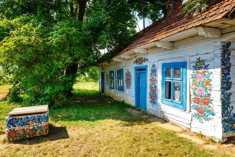 Kleurrijk die huis met bloemen op muren en zonnewijzer in het dorp van Zalipie, Polen worden geschilderd Het royalty-vrije stock afbeeldingen