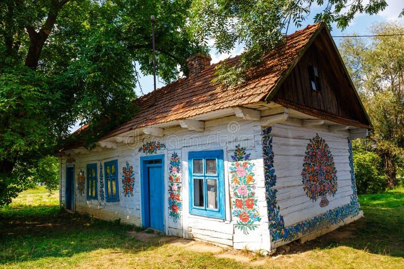 Kleurrijk die huis met bloemen op muren en zonnewijzer in het dorp van Zalipie, Polen worden geschilderd Het royalty-vrije stock foto