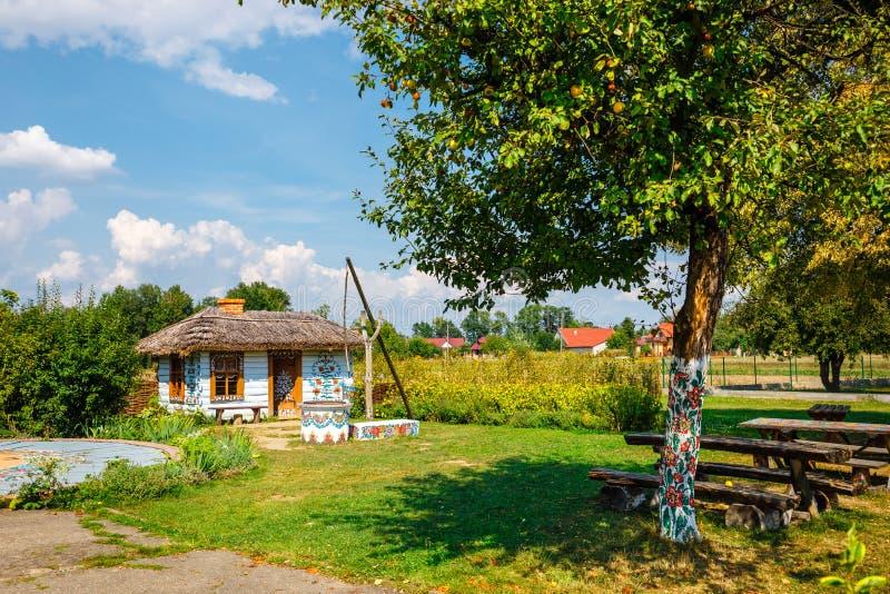 Kleurrijk die huis met bloemen op muren en zonnewijzer in het dorp van Zalipie, Polen worden geschilderd Het stock foto's
