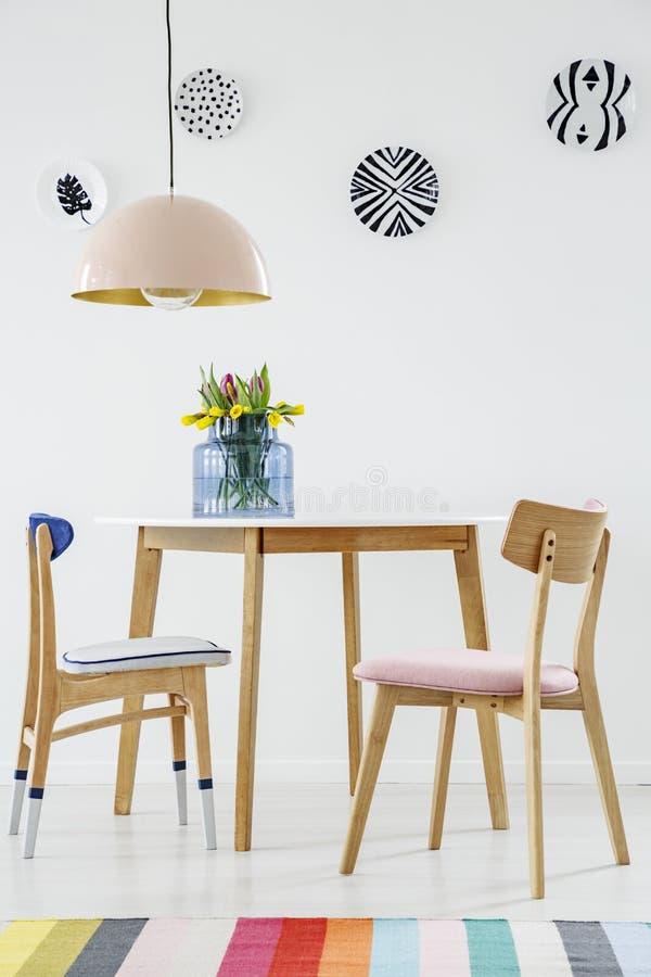 Kleurrijk eetkamerbinnenland met een lijst, stoelen, gestreepte deken, royalty-vrije stock afbeelding