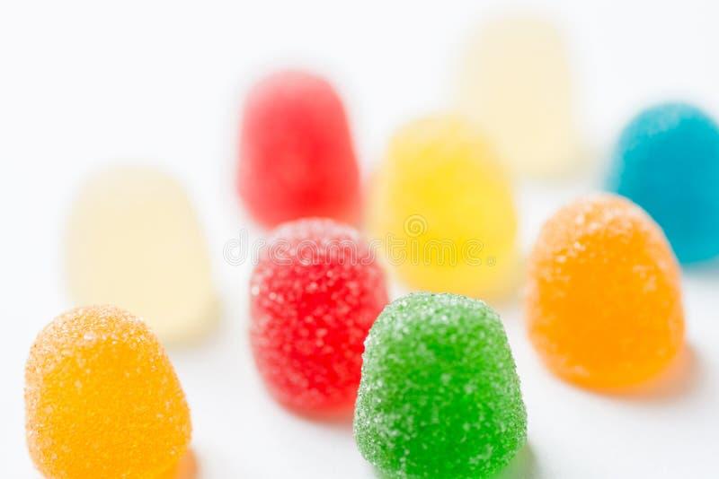 Kleurrijk geel rood oranje groen kleverig die geleisuikergoed met suiker op witte achtergrond met een laag wordt bedekt De pret v royalty-vrije stock foto