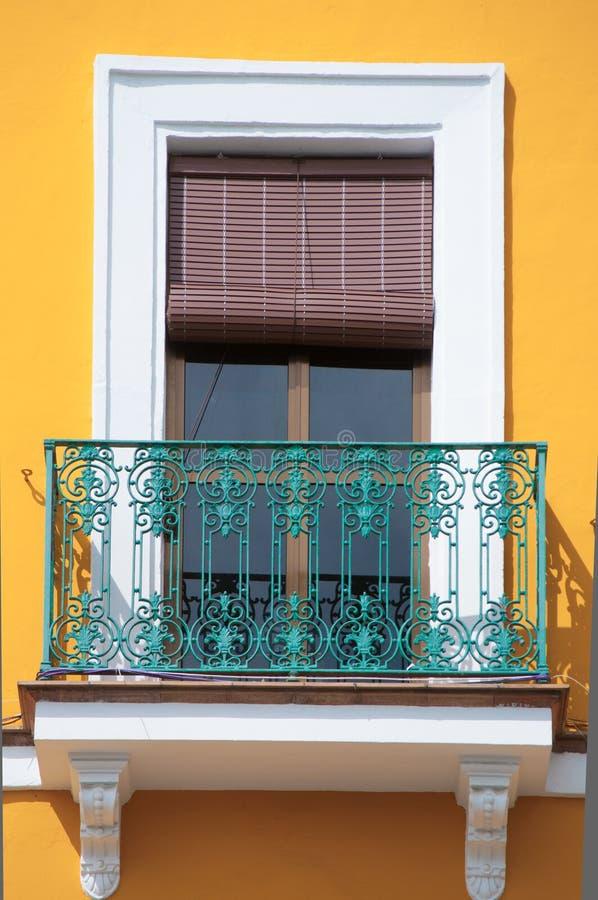 Kleurrijk geel venster en turkoois balkon in Spanje stock fotografie