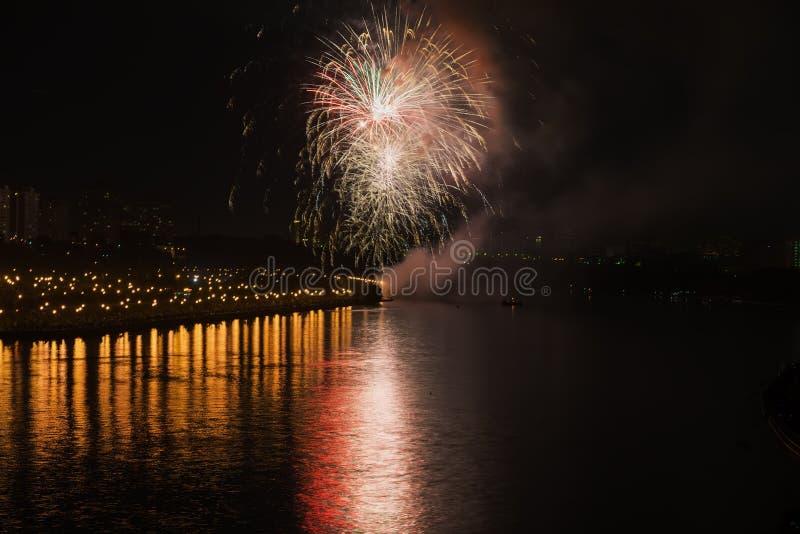 Kleurrijk helder vuurwerk, begroeting van diverse kleuren in nachthemel met bezinning in het meer abstracte vakantie royalty-vrije stock foto
