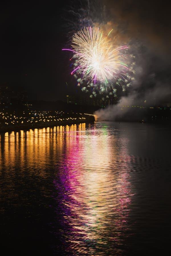 Kleurrijk helder vuurwerk, begroeting van diverse kleuren in nachthemel met bezinning in het meer abstracte vakantie stock foto