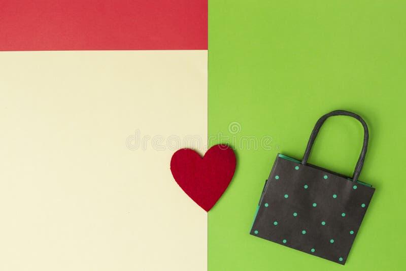 Kleurrijk het winkelen zak en hart op groen, rode, gele gekleurde document achtergrond Hoogste mening Exemplaarruimte voor tekst stock fotografie