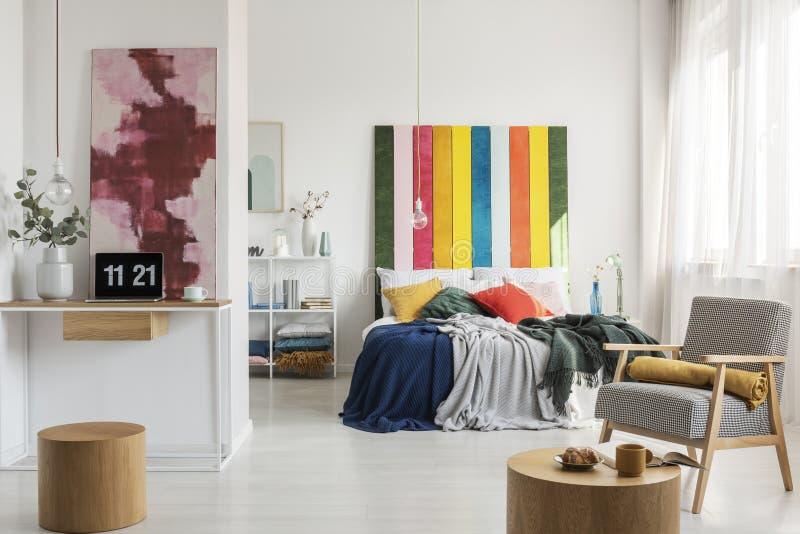 Kleurrijk hoofdeinde in het bed van de koningsgrootte met hoofdkussens en deken en huisbureau met laptop en vaas met bloemen stock foto's