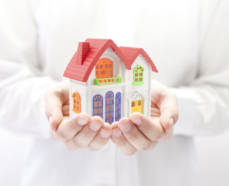 Kleurrijk huis in handen royalty-vrije stock foto