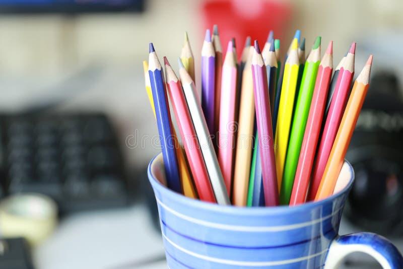 Kleurrijk kleurpotlood in de blauwe kop op het werklijst royalty-vrije stock foto's