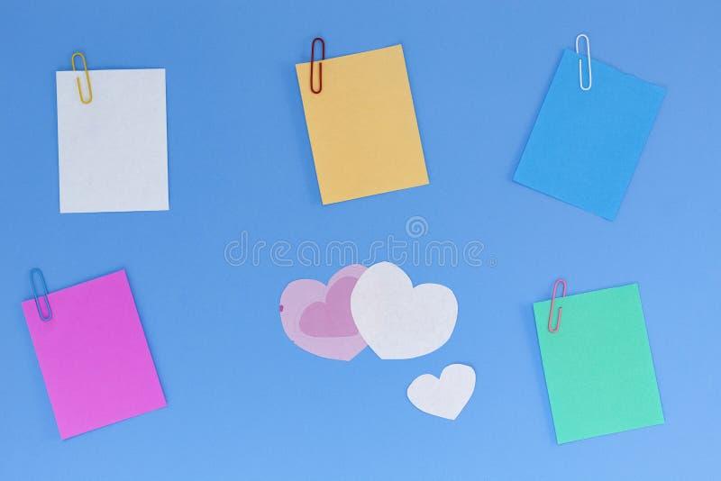 Kleurrijk leeg document nota en document hart op blauwe achtergrond, FO stock fotografie