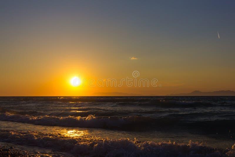 Kleurrijk leeg zeegezicht met glanzende overzees over bewolkte hemel en zon tijdens zonsondergang in Rhodos, Griekenland stock afbeeldingen