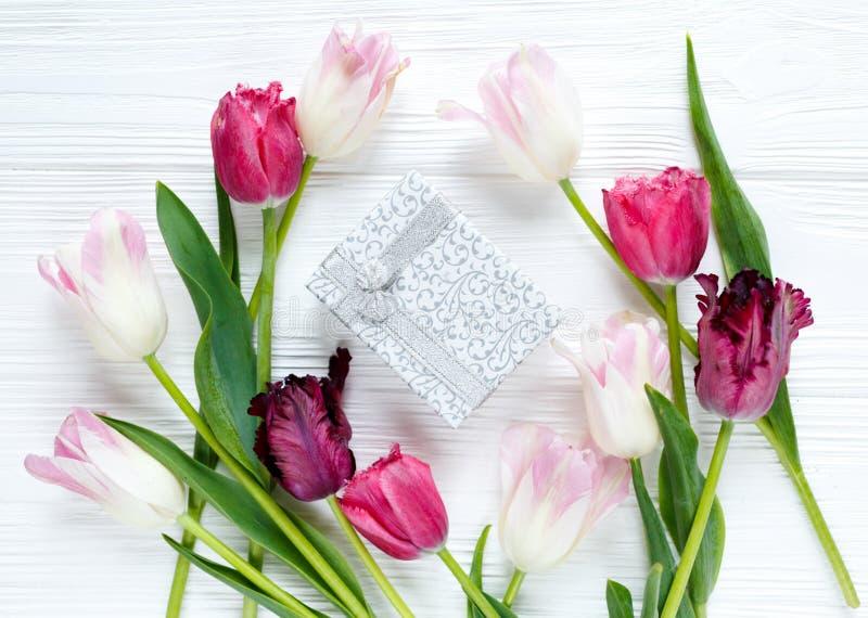 Kleurrijk mooi tulpen en giftvakje op de witte houten lijst Valentijnskaarten, de lenteachtergrond bloemenspot omhoog met copyspa stock foto's