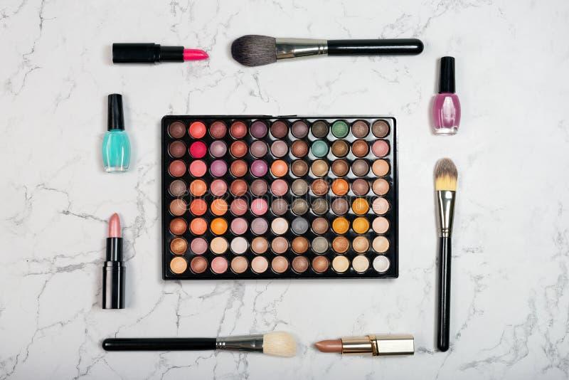 Kleurrijk oogschaduwpalet met borstels, lippenstift en spijkervernis op marmeren achtergrond royalty-vrije stock foto's